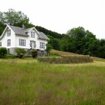 Norsk farmhouse, making hay the old fashioned way out front